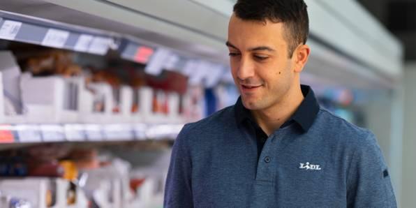 Служител магазин в брандирана тениска в сектор охладени