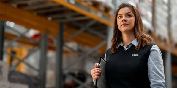 Жена групов ръководител в централен склад с папка под мишница между две редици стелажи