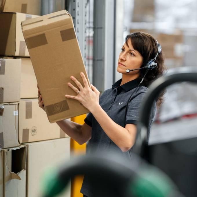 Жена складов служител подрежда кашони със стока в централен склад