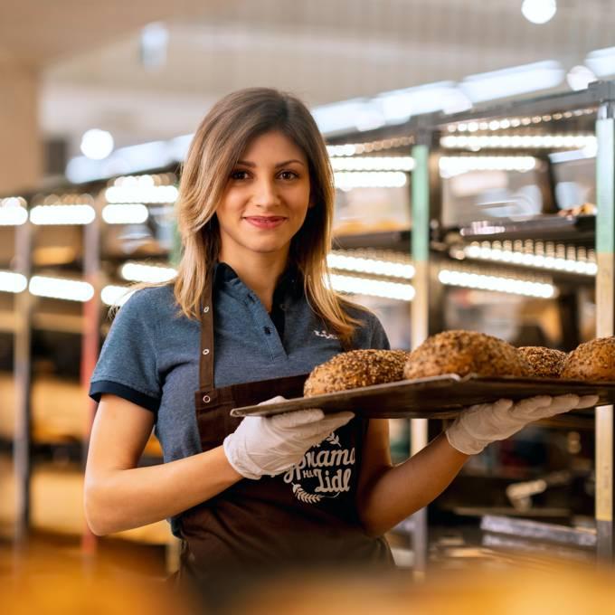 Жена касиер продавач във фурната на Лидл с табла с хляб в ръце