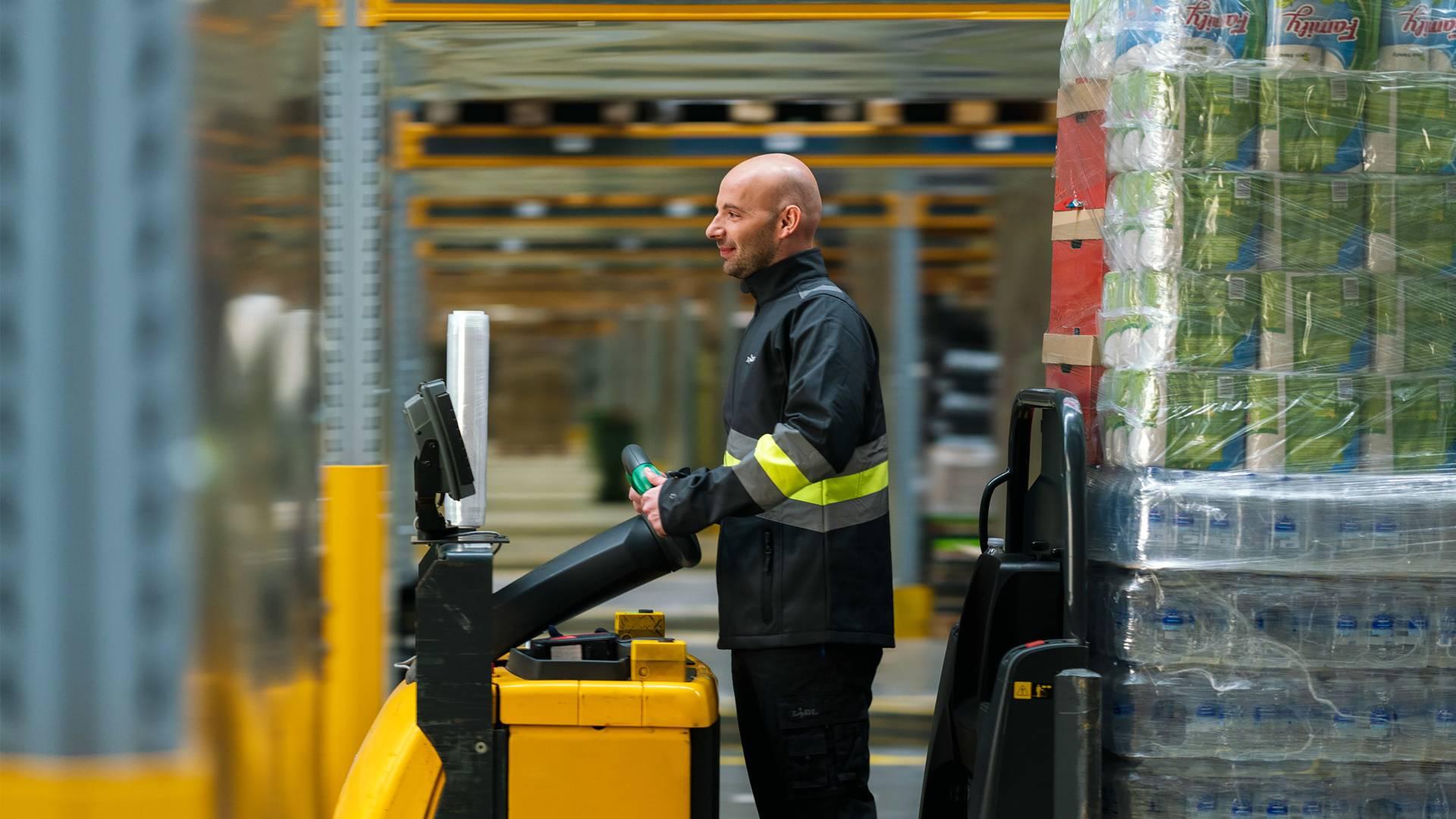 Служител в склад управлява мотокар със стоки от поръчка