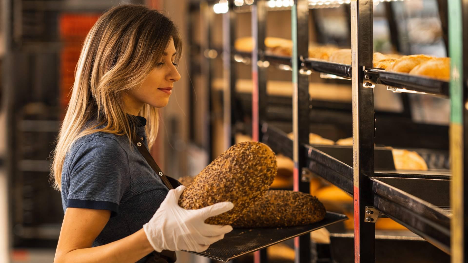 Служителка в магазин подрежда хляб от фурната на Лидл