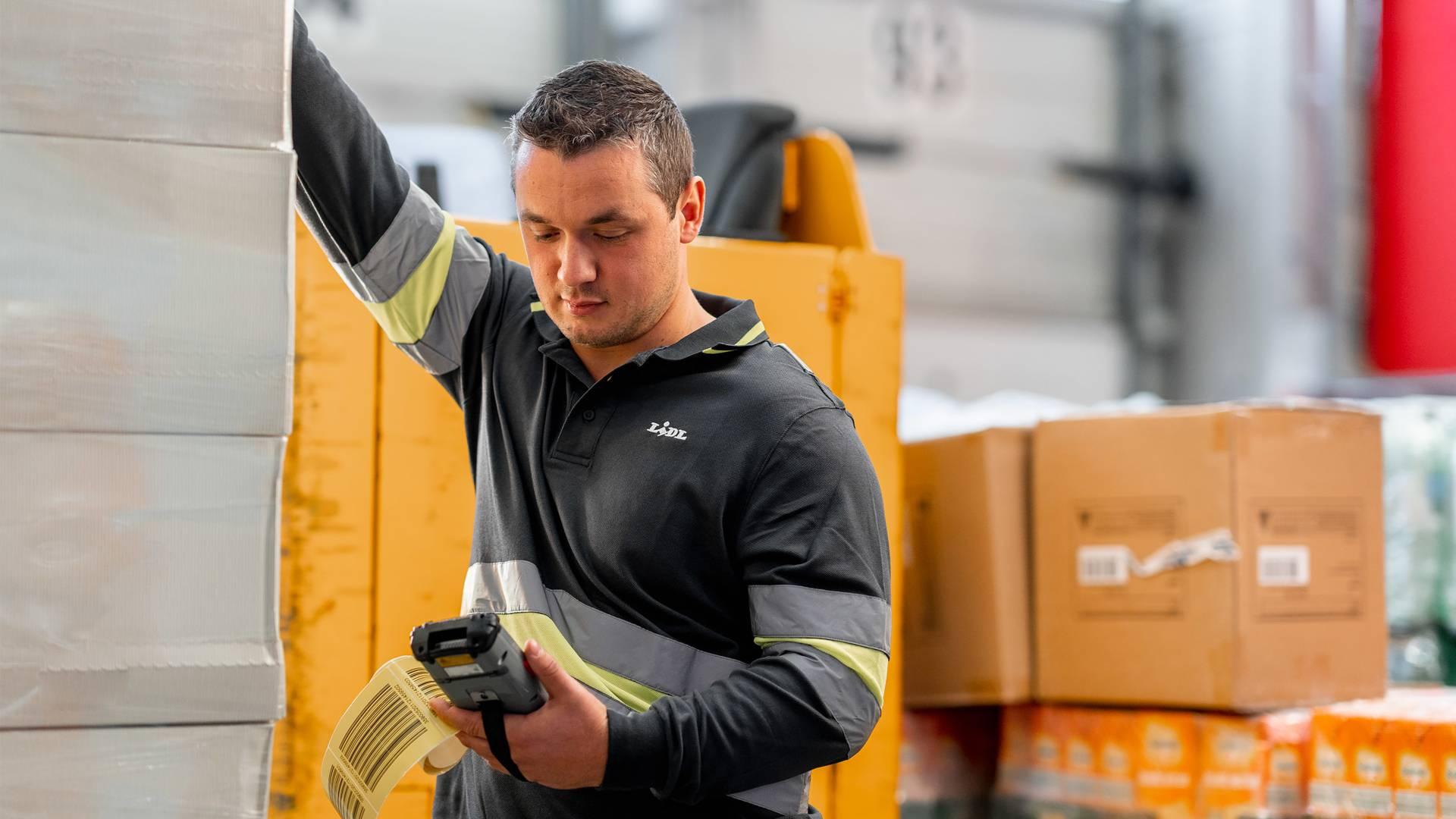 Служител складово обслужване проверява кашони със стока