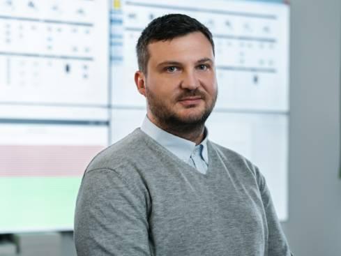 Мъж служител отдел информационни технологии пред екрани в централен офис