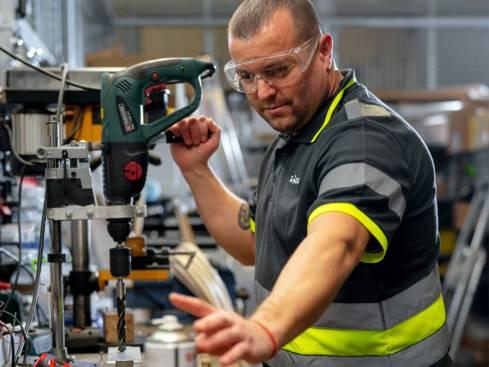 Мъж техник с предпазни очила работи с дрелка в централен склад