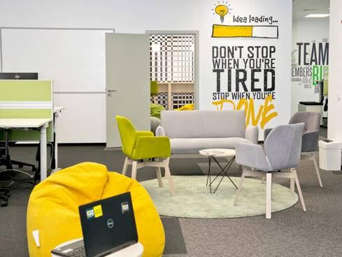 Офис Лидл Диджитал кръгла маса диван и столове в центъра пуф и лаптоп на близък план