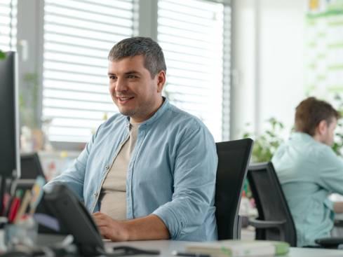 Графични дизайнери от отдел маркетин и реклама седнали пред компютри в офис