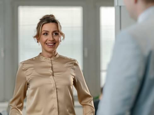 Жена служител разговаря с колега в централен офис