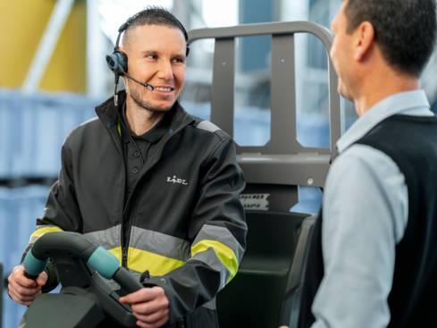 Мъж складов работник на мотокар разговаря с групов ръководител централен склад