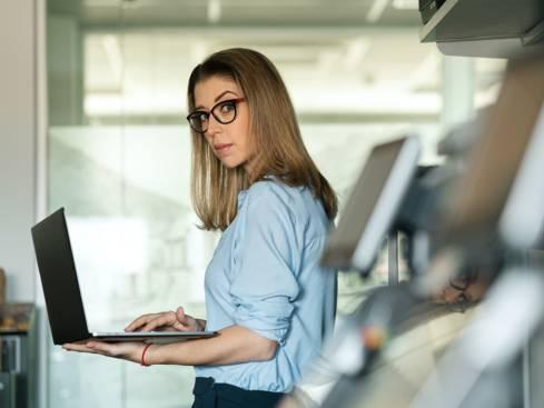 Жена служител в отдел информационни технологии с лаптоп в ръце