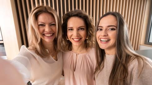 Три усмихнати жени селфи