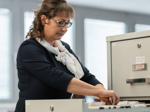 Служителка от отдел администриране на персонал подрежда досиета в шкаф