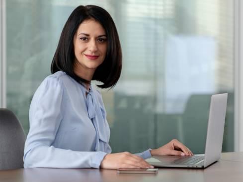 Жена в заседателна зала седнала пред лаптоп и мобилен телефон