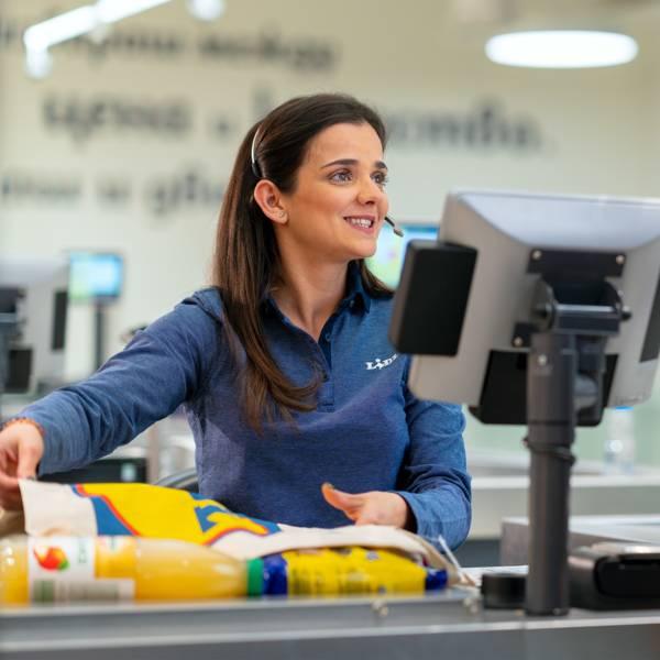 Жена касиер продавач маркира торбичка Лидл на каса усмихната към клиент