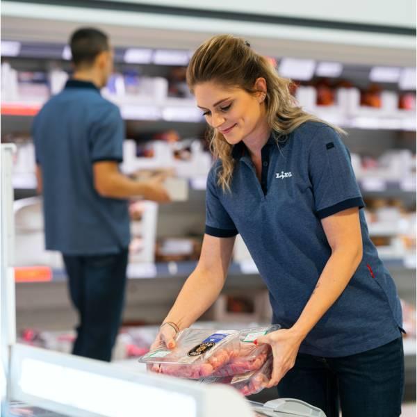 Жена касиер продава зарежда месо в сектор охладени в магазин Лидл зад нея мъж касиер продавач зарежда колбаси