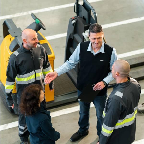 Групов ръководител в централен склад говори на трима складови работници пред мотокар