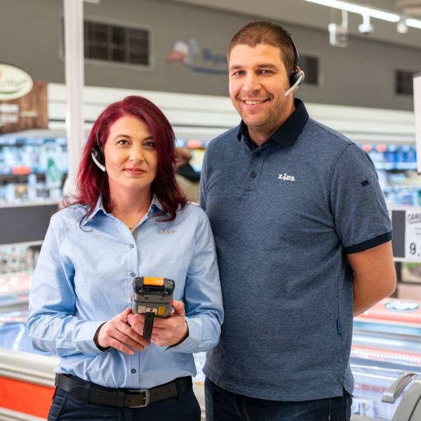 Жена мениджър филиал с устройство за поръчка на стоки в ръце до мъж касиер продавач пред сектор замразени в магазин