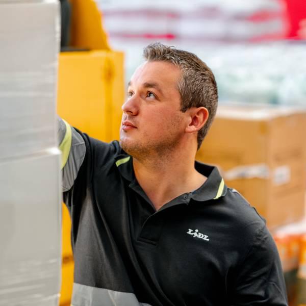 Мъж складов работник проверява стока в централен склад