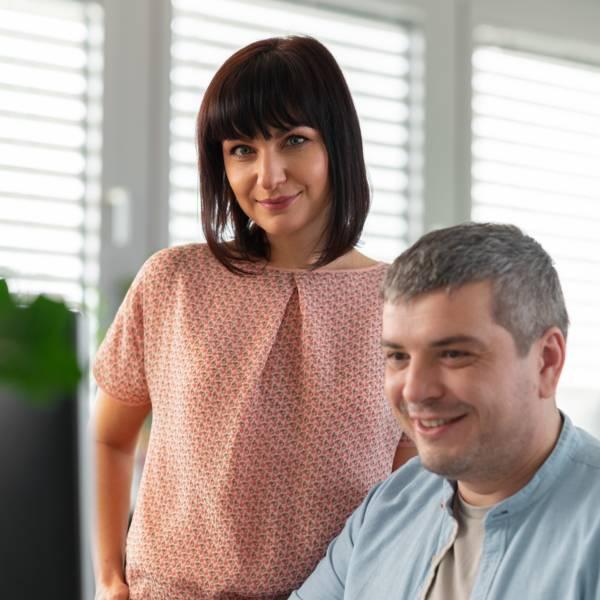 Мъж графичен дизайнер от отдел маркетинг и реклама показва изработен образ на монитор на своя колежка в централен офис