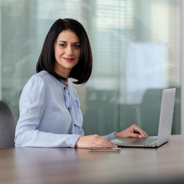 Жена служител в отдел продажби в заседателна зала пред лаптоп и мобилен телефон в централен офис
