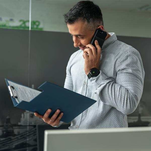 Мъж служител в отдел логистика облечен в сива риза разговаря по мобилен телефон докато разглежда документ в папка