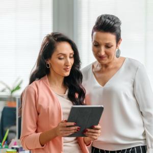 Две жени служители в отдел човешки ресурси разговарят докато гледат в екрана на таблет в централен офис