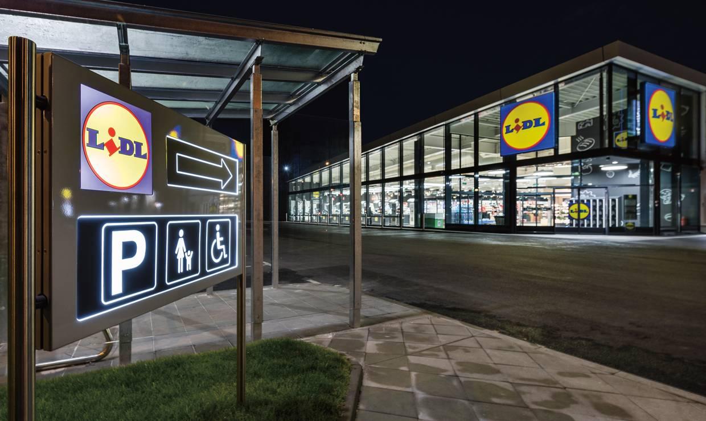 Новопостроен магазин Лидл през нощта вляво на преден план табела сочеща към паркинг