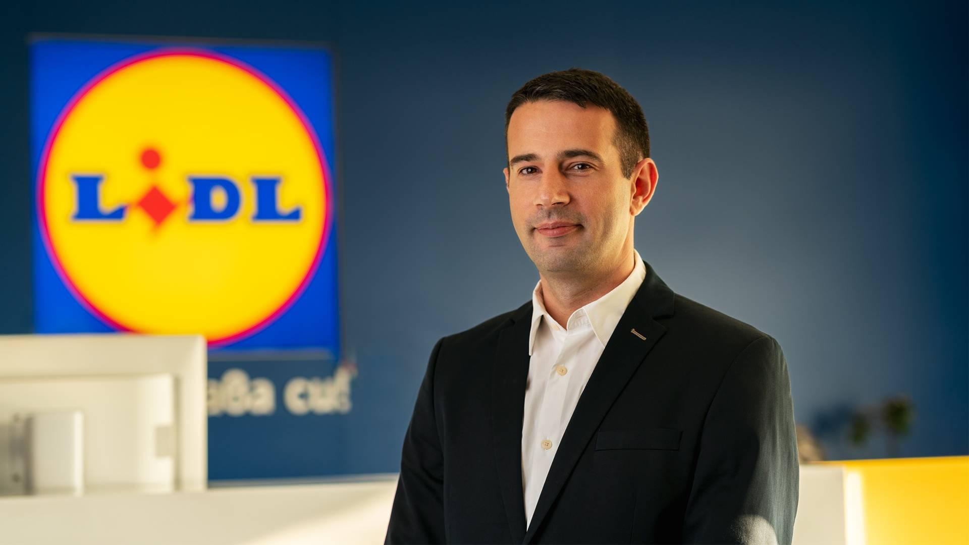 Мъж ръководител отдел маркетинг и реклама в сако и риза пред лого на Лидл в централен офис разказва своята история на успеха