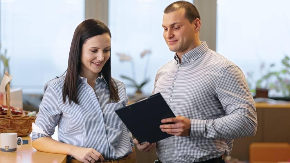 Мъж и жена облечени в ризи обсъждат документ в папка в ръцете на мъжа